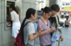 photo of people taking a survey in front of an ATM