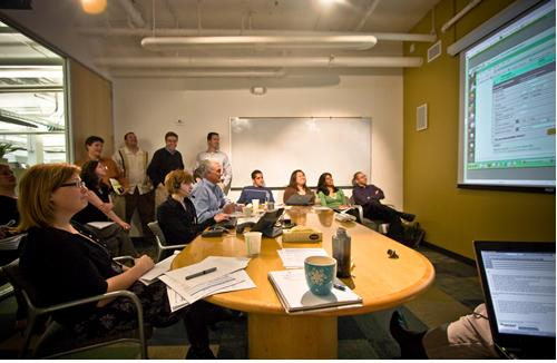 clients in a meeting room watching a presentation projected against a wall