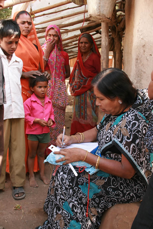 A woman writes on a medical form while a family watches