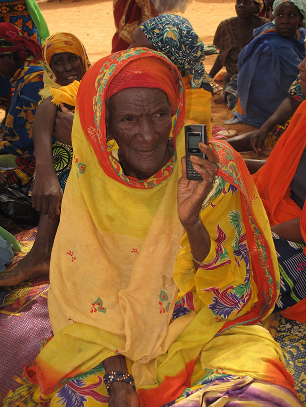 An older woman, sitting in a group with others, holds up a mobile phone.