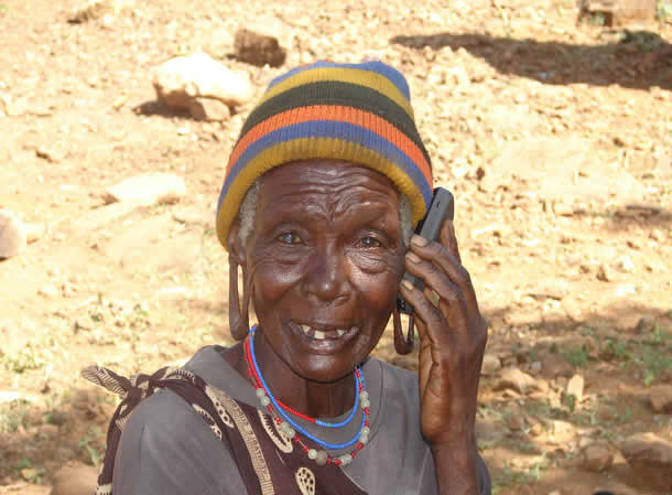 A woman holds a mobile phone to her ear.