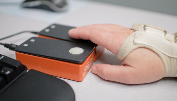 A hand, wearing a brace, presses a switch to operate a computer.
