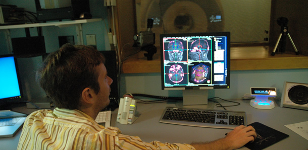 man looking at MRI results on a computer