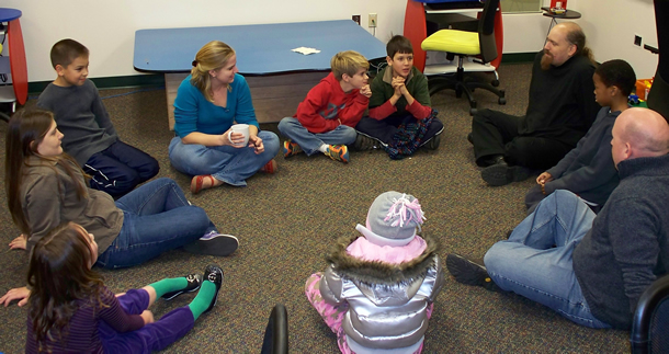 children and adults sitting in a circle