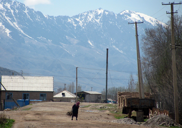 Photo: a woman walking on a dirt road, with mountains in the background