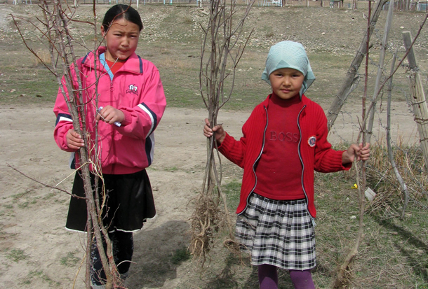 Photo of two girls holding saplings
