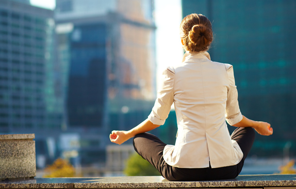 Woman in business clothes meditating, city buildings in the background.