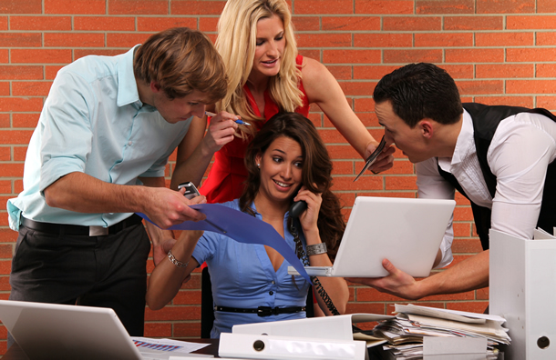 A woman at a desk with assistants around her clamoring for attention