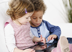 Two young children using a tablet