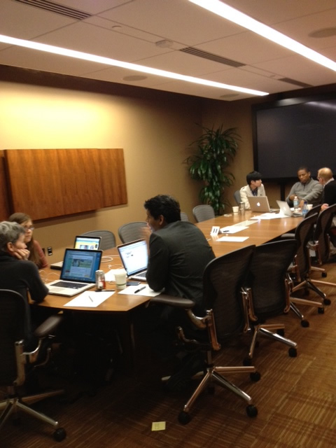Two groups, working at different ends of a long conference table