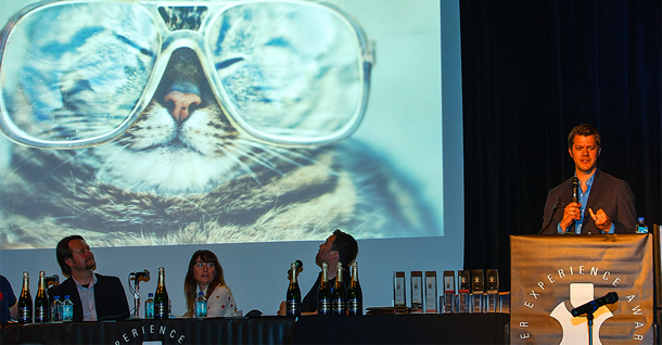 Speaker at a podium. The screen shows a photo of a cat in glasses.