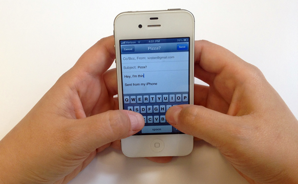 Hands typing message on iPhone, with Sent from my iPhone on the screen