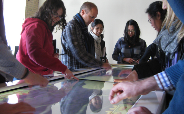 People playing a game around a table surface.