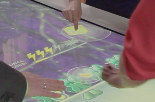 Closeup of hands playing on the interactive surface