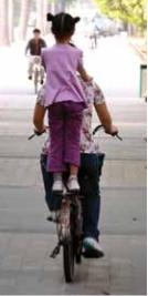 girl standing on back of bicycle
