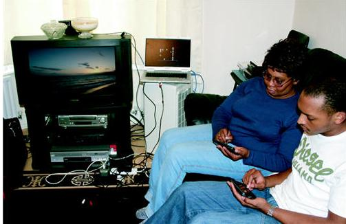 photo of users sitting on a couch using a PDA