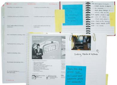 photograph of notebooks with pictures and post-it notes attached