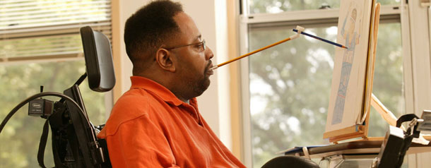 A man in a wheelchair unable to use his hands drawing a picture using a mouth stick