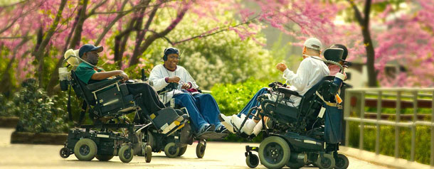 Four men in wheelchairs socializing in a park on a spring day