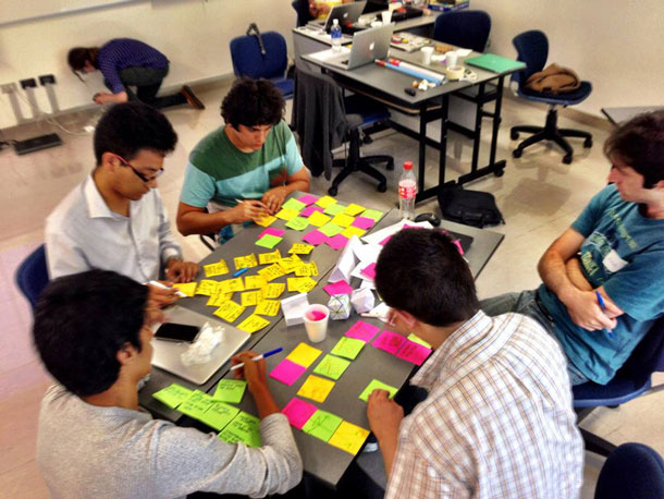 A small group works around a table, with colored Post-it notes.