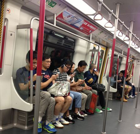 A row of passengers on a train. Each passenger uses a mobile device.