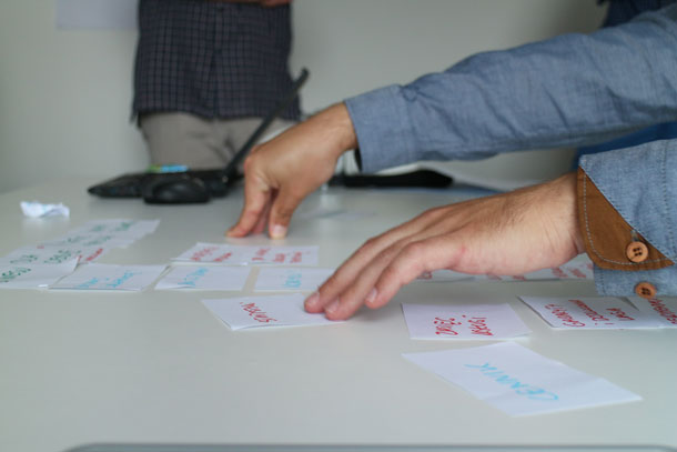 A person rearranges cards on a table.