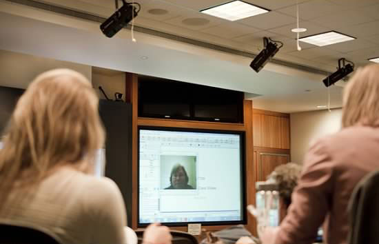 A photo showing a student's face on a large screen, while other students watch from their seats.