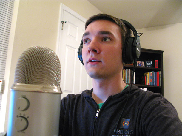 Photo of Wesley recording a podcast, wearing headphones and speaking into a large mic.
