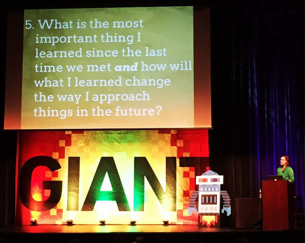 """Photo of Leslie Jensen-Inman. A presentation slide displayed in the background says, """"What is the most important thing I learned since the last time we met and how will what I learned change the way I approach things in the future?"""""""