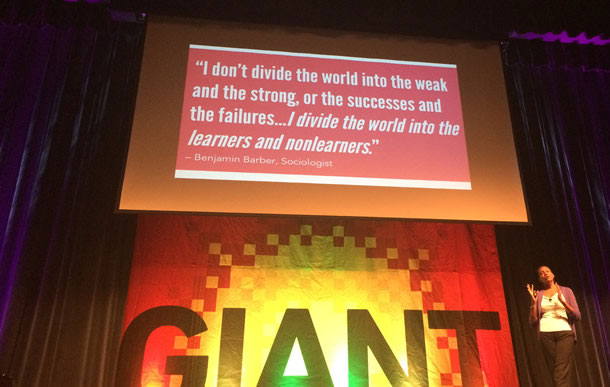 """Photo of Denise Jacobs. A slide in the background has a quote from Sociologist Benjamin Barber. """"I don't divide the world into the weak and the strong, or the successes and the failures…I divide the world into the learners and non-learners."""""""