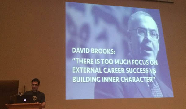 """Photo of Giovanni Ulloa. A slide in the background has a quote that says, """"There is too much focus on external career success versus building inner character."""""""