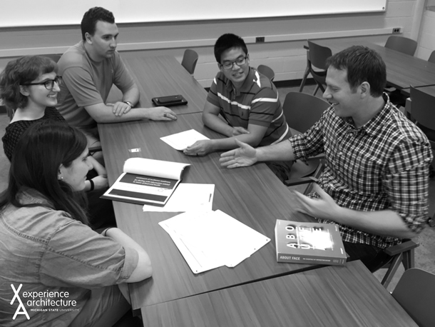 A group of people having a discussion around a table.