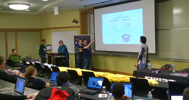 A group of students stand at the front of a classroom, showing their ideas on a projection screen.