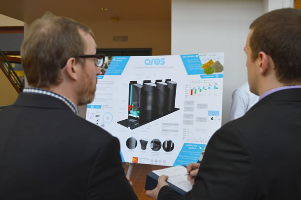 Two people look at a poster of a design concept. One has a form on which he is making notes.