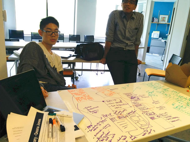 Two students sit around a table looking at a sketch of design ideas on a large piece of paper.