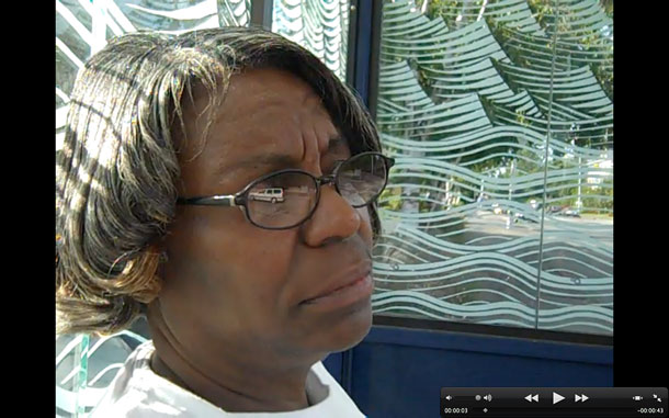 A screen capture of a video where a woman waits at a bus stop.