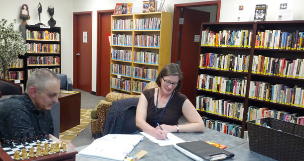 Two people at a table in a community center library. The room is informal but comfortable looking with books lining the walls.