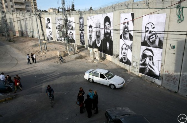 A photograph of the wall, showing the scale of the images, which are up to 10 feet tall.