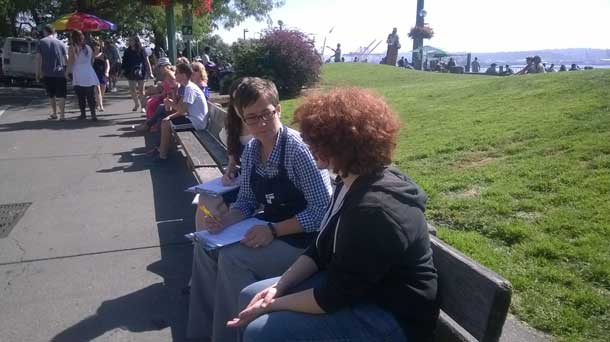 Researcher, in identifying apron, holds a session guide in her lap while she talks to a visitor to the park.