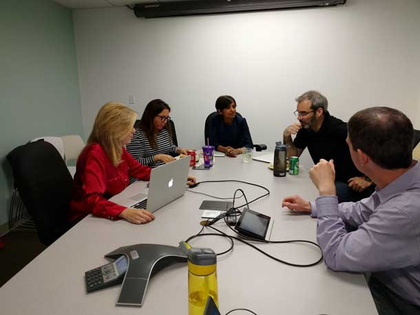 Five people around a conference table.