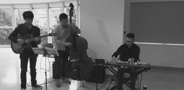 A trio of musicians playing guitar, bass and keyboard