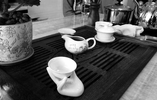 A tea set arranged on a tray. one cup is held in a porcelain hand