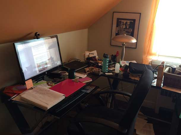 Image of a home office: a cluttered desk with a large monitor, webcam, and comfy chair.
