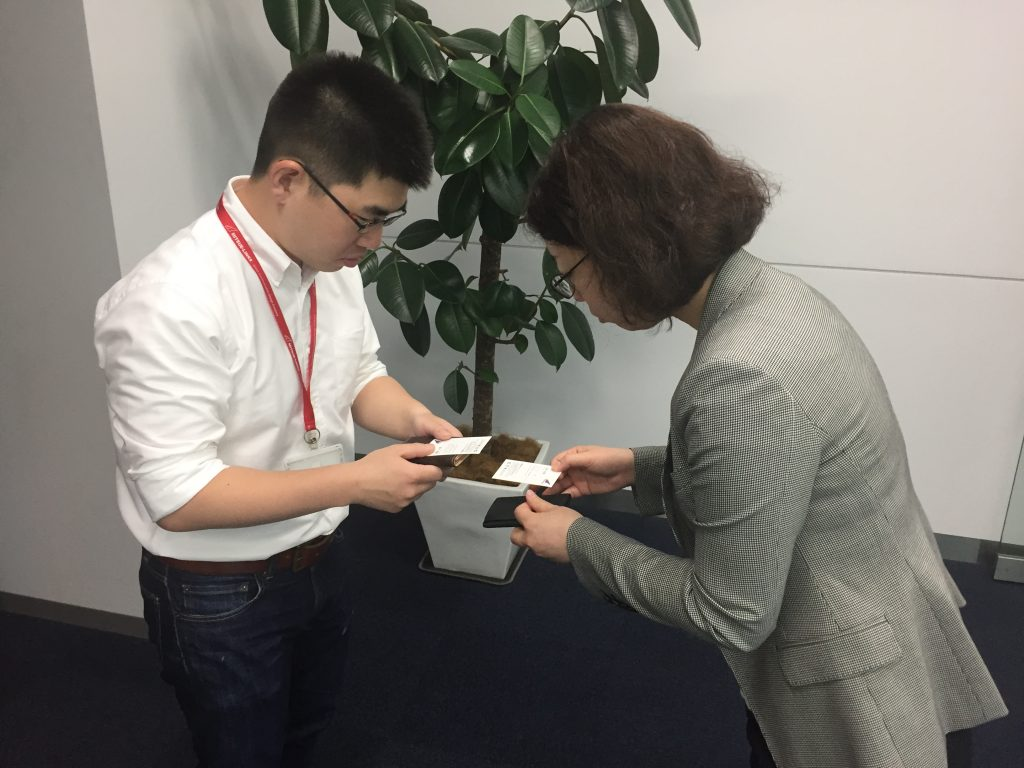 Picture shows two Japanese business people exchanging business cards, a common start to conducting business in Japan.