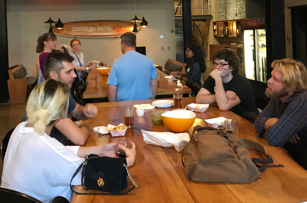 A photo of a group of members from Triangle UXPA discussing UX trends in a happy hour setting