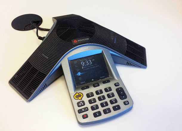 A desktop Polycom conference phone showing the buttons and display screen.