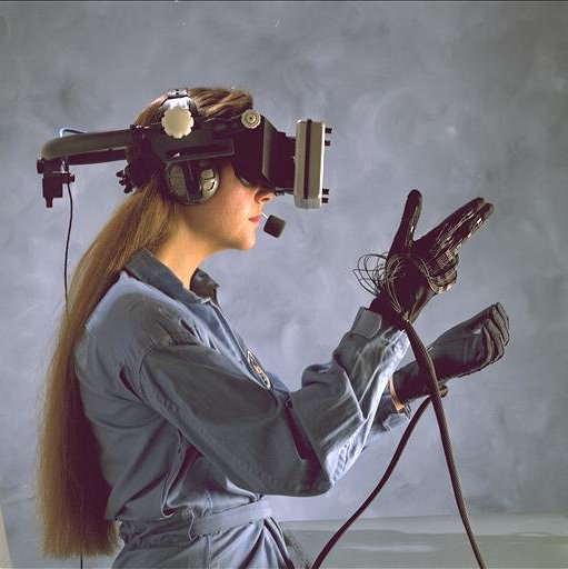 A woman wearing a helmet with a screen in front of her eyes, and gloves with sensor cables.