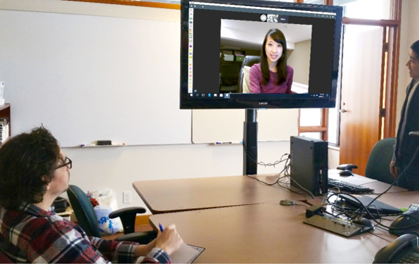 image of two team members on either side of a monitor, where a third team member is on the screen.
