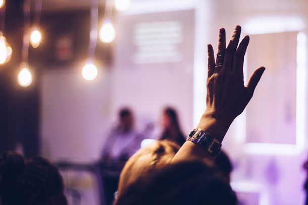 A person in a conference setting raising a hand to ask question.