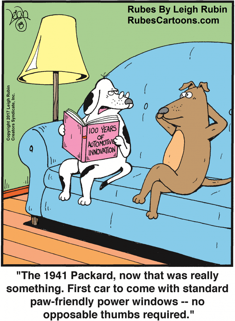 """Two dogs sitting on a sofa. One of them is holding a book titled """"100 years of automotive innovation"""""""
